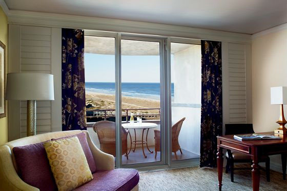 A love seat and desk in front of a sliding glass door leading to a furnished patio overlooking the ocean