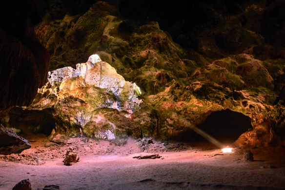 The sun shines through a large opening in a rocky cave