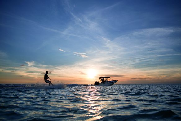 A boat carries a jet-skier across the water at sunset