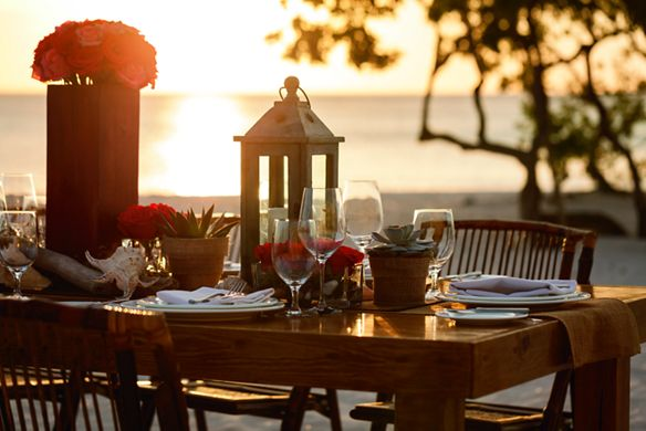 An elegantly dressed long dining table on the beach at sunset