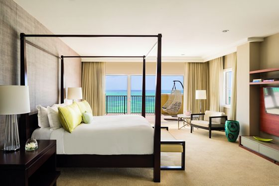 A four-poster king bed, flat-screen TV, sofa bench and a patio with a hanging cocoon chair and ocean view