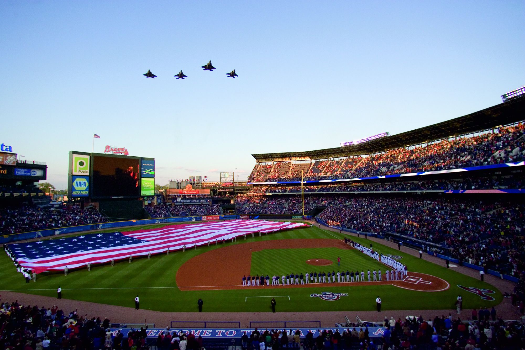 Jets fly over a baseball field where a large American flag is being unfurled