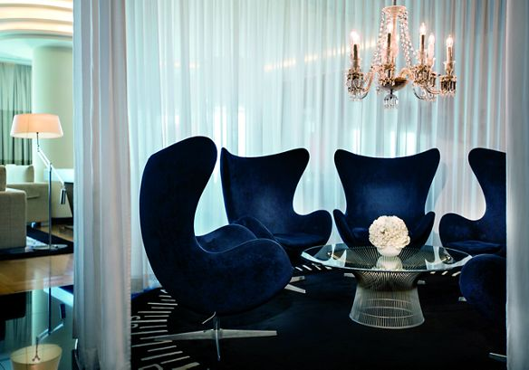 Five cocoon-like chairs in navy velvet form a circle in a semi-private space within the Club Lounge
