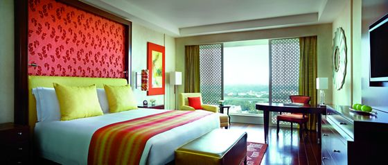 Guest room accented with reds and yellows and featuring a king bed and ceiling-height headboard of red upholstery