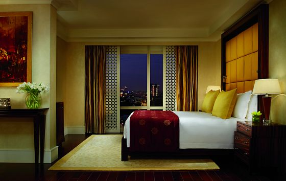 A king bed next to a floor-to-ceiling window with an open carved wood screen and curtains revealing a city at night