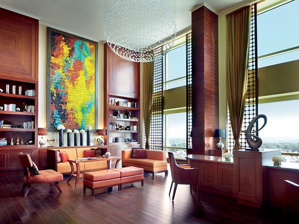 Room with a seating area, floor-to-ceiling windows, a reception desk, a round chandelier, bookshelves and a painting