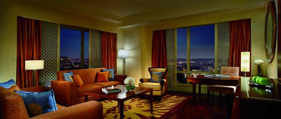 Living room with expansive windows and skyline views on two walls, hardwood floors and a palette of gold, red and orange