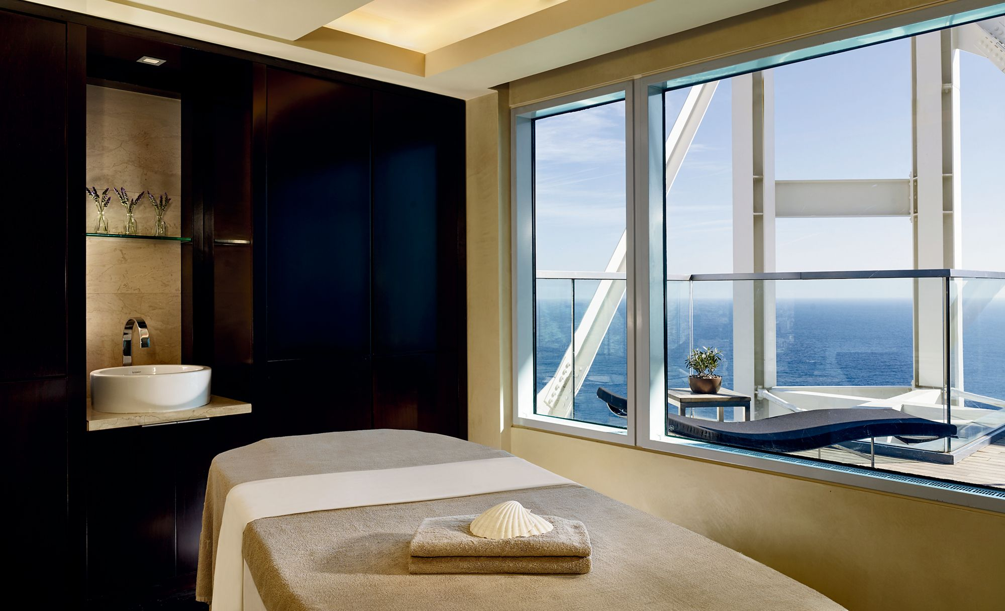A room with a massage table, bowl sink and large windows overlooking a furnished terrace and the sea
