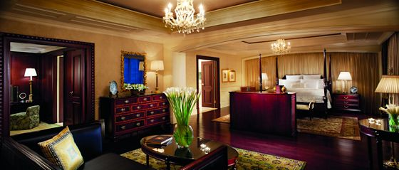 A four-poster bed overlooks a large bedroom with a seating area, elegant furnishings and chandeliers
