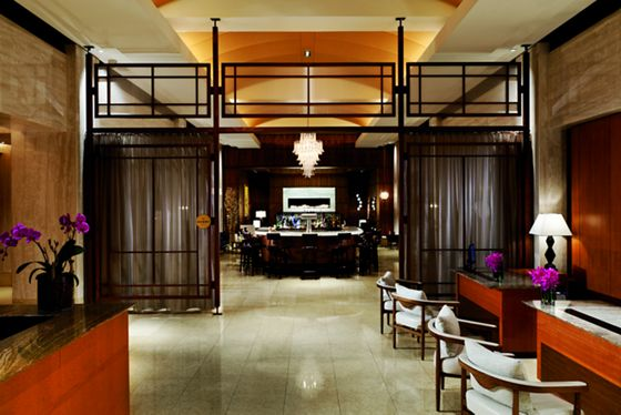 View of reception desks and chairs on one side and a rounded bar with stools and a chandelier hanging above in the back