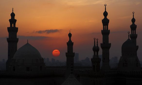 A building with domes and minarets silhouetted against a setting sun