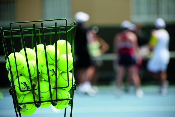 A wire basket holding tennis balls