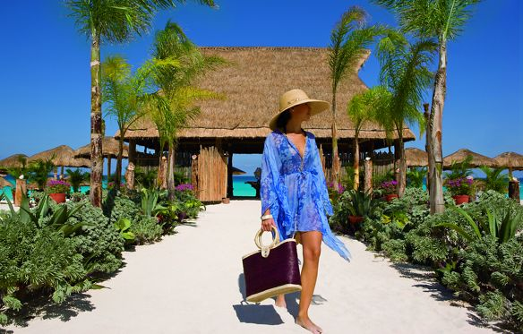 A woman in beach attire walks along a sandy path lined with palm trees and plants