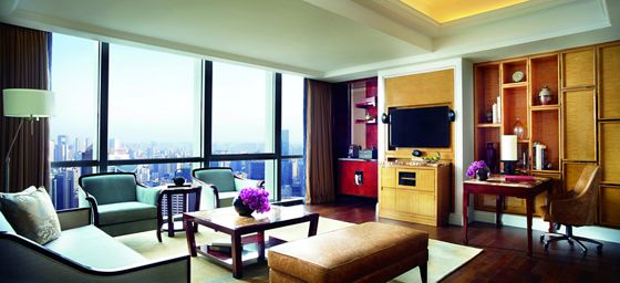 Sitting room with floor-to-ceiling windows overlooking the city at night, plush seating and a wall-mounted flat-screen TV