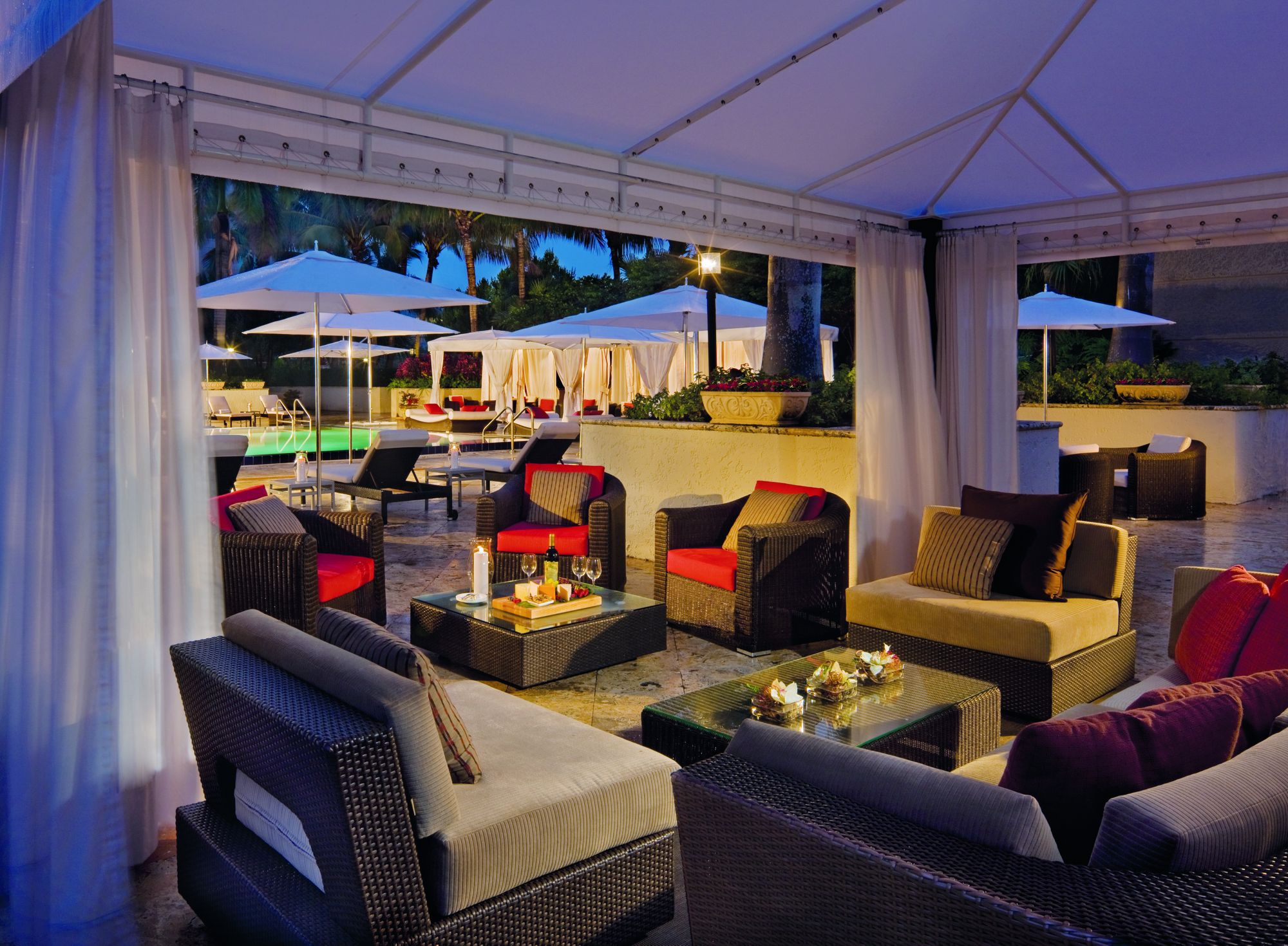 Private poolside pavilions offer comfortable seating for group gatherings.