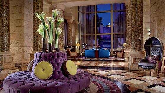 Hotel lounge with round, purple pillow lounge chair adorned with a floral plume.