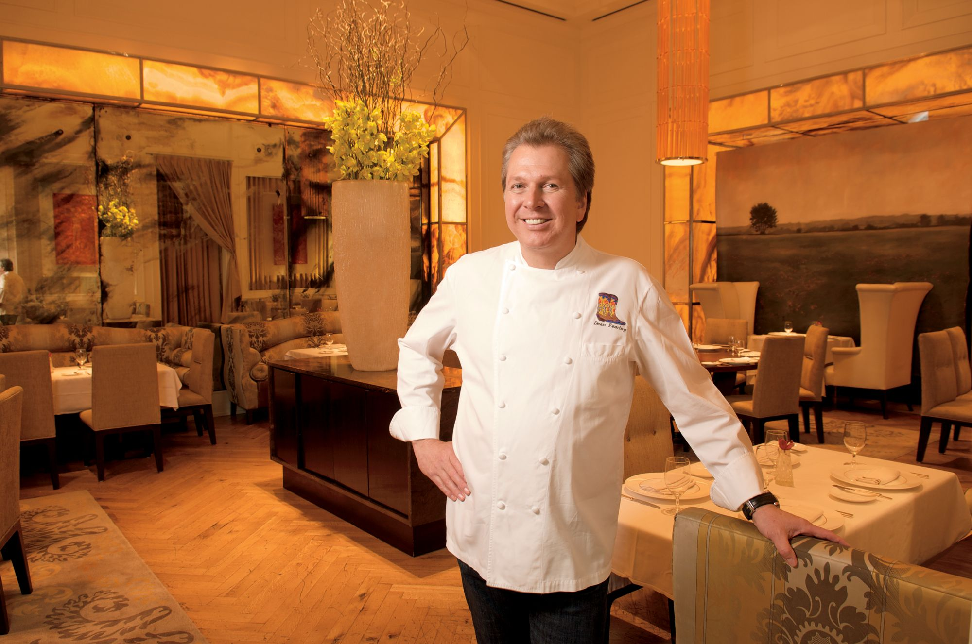 Smiling man in chef's whites standing with his arms crossed in a restaurant dining room