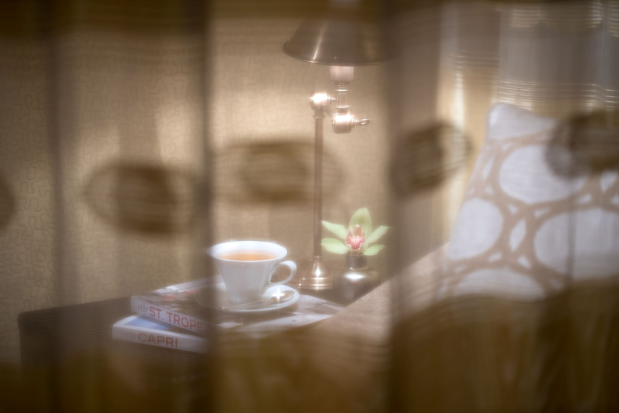 View through a sheer curtain of a cup of tea