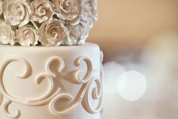 Close-up of the top tier of a wedding cake featuring a topper of white roses executed in frosting