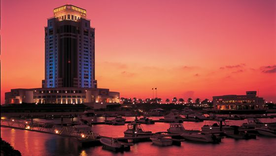 Gently illuminated hotel glows against a bright pink and orange sunset with the marina in the foreground