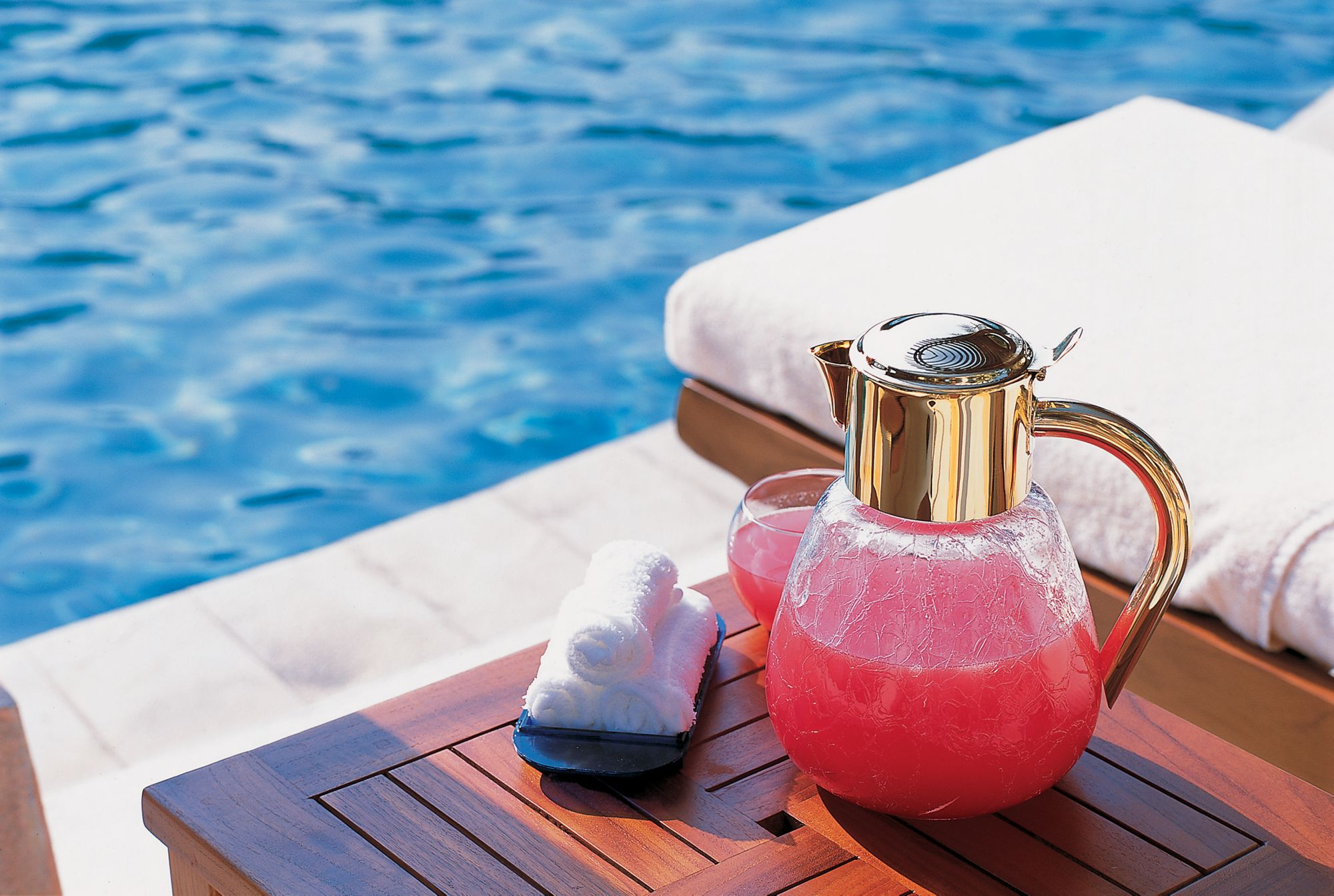 A clear jug of pink juice and three washcloths rest on a table between lounge chairs next to the pool
