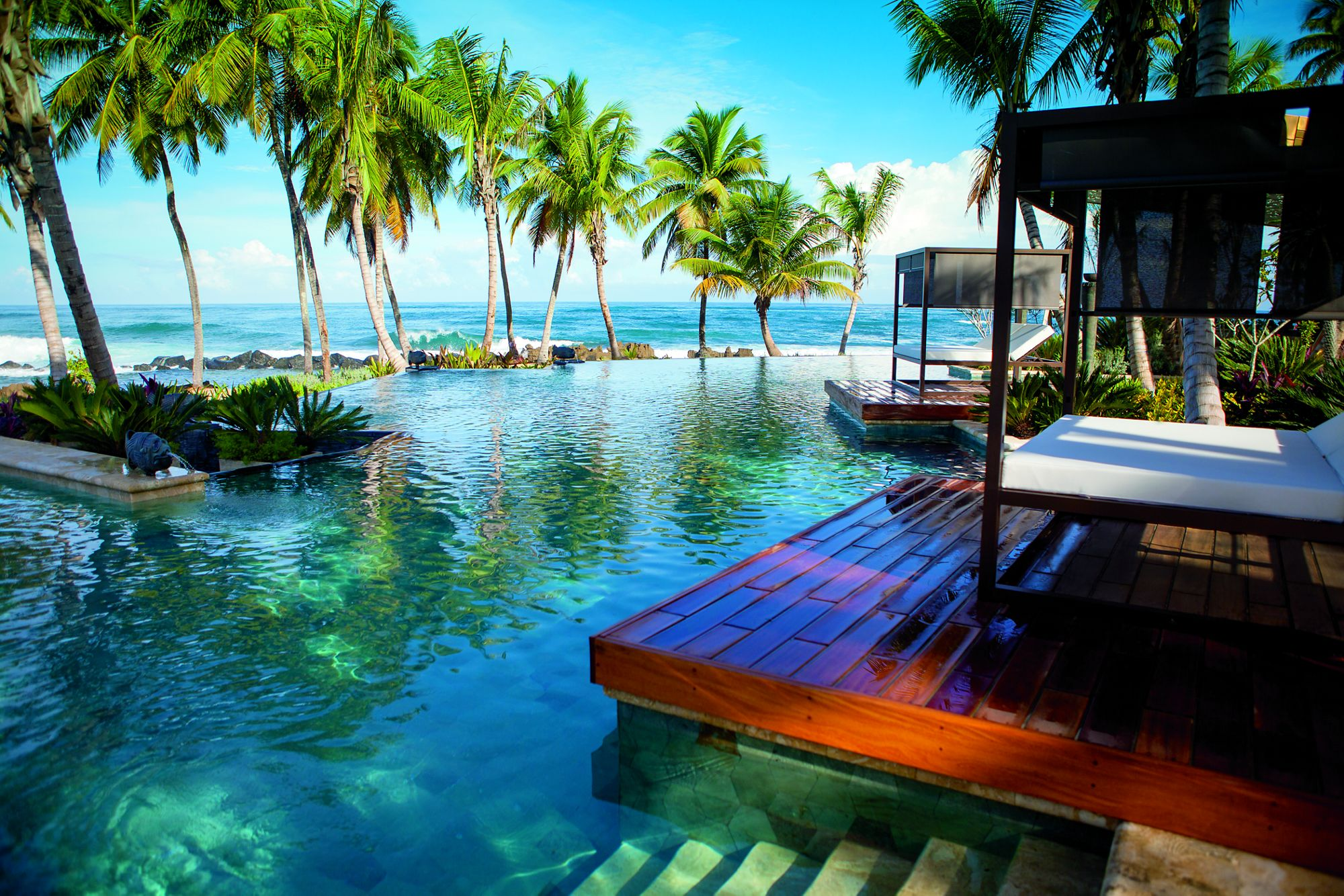Infinity pool with comfortable cabana lounges and the ocean in the near background