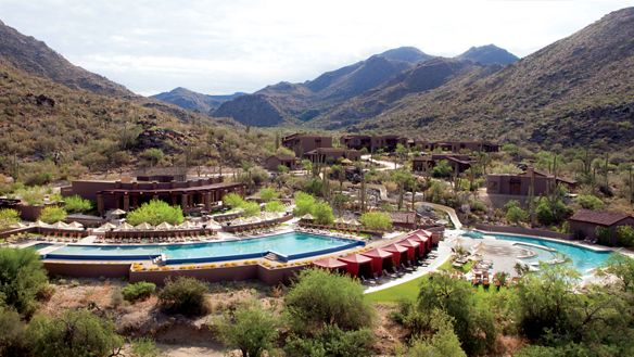 Mountains overlooking a resort with pools