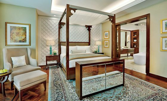 Suite bedroom with dark wood four-post bed, mirrored dresser, seating area and quilted wall panel