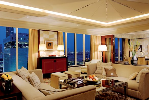 Living room with light furnishings, dark wood accents and a wall of floor-to-ceiling windows overlooking the city at night