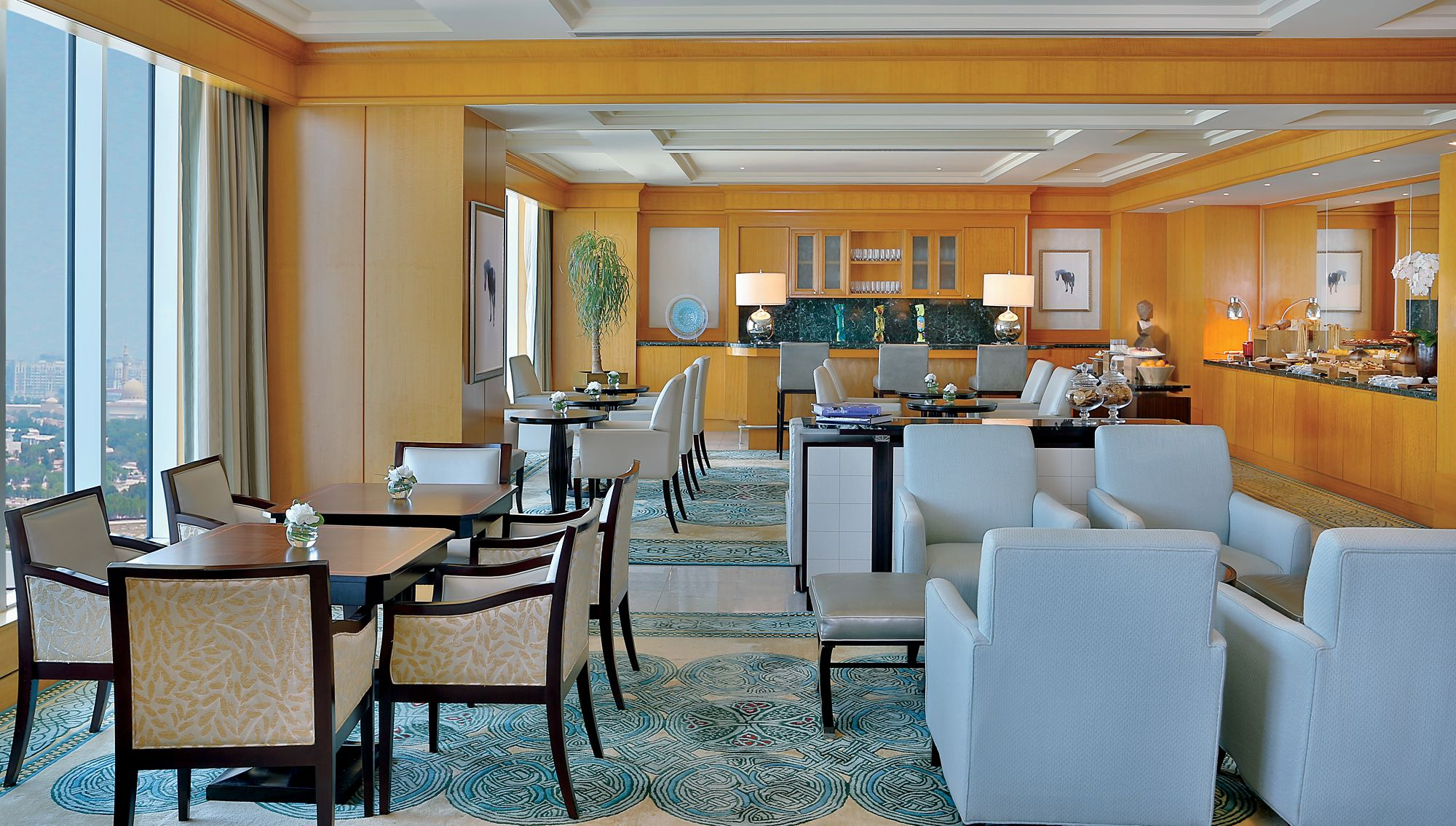 Club Lounge featuring floor-to-ceiling skyline views, flexible seating, honey-colored wood accents and culinary presentations