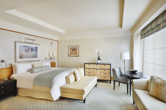 Guest room bathed in natural light and outfitted with a king-size bed, sofa, desk and a color palette of cream and blue-gray