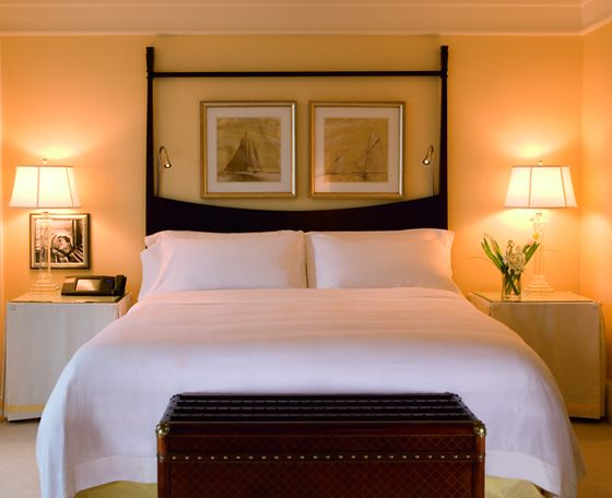 A king bed with two nightstands and lamps, two framed boat pictures on the wall and a wood trunk at its foot