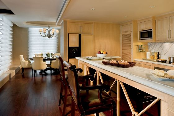 A large kitchen with a dining table, island and wood-paneled cabinets
