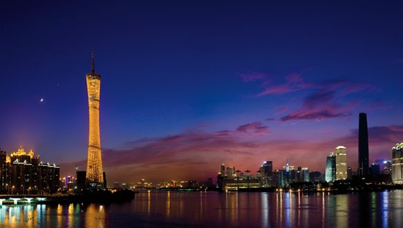 A tall building overlooks a river at night