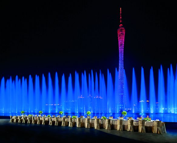 A long dining table set up next to a fountain at night