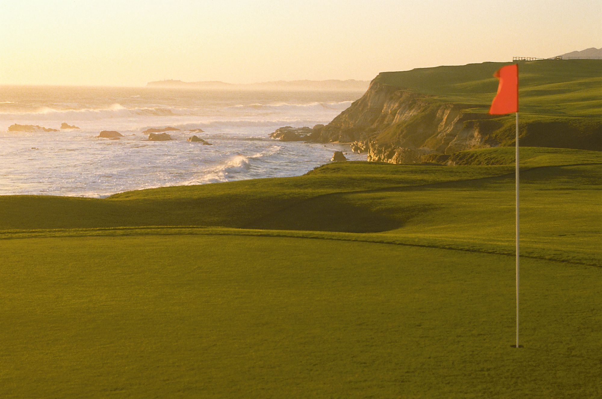 A flag indicates the 18th hole on a golf course, which sits next to the ocean 26. HalfMoonBay_00169