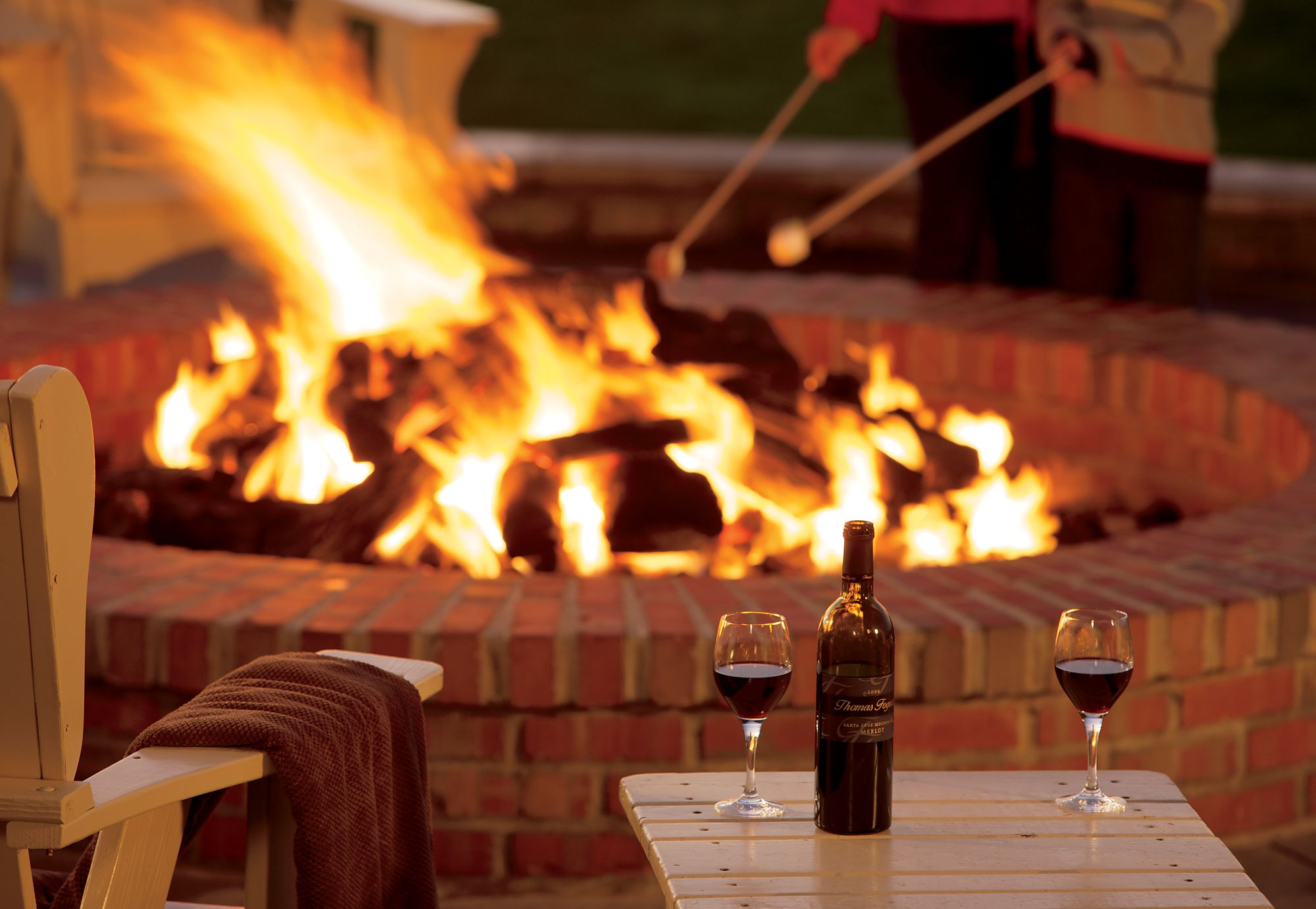 Close-up of a bottle of wine and two filled glasses on a table in front of a fire pit
