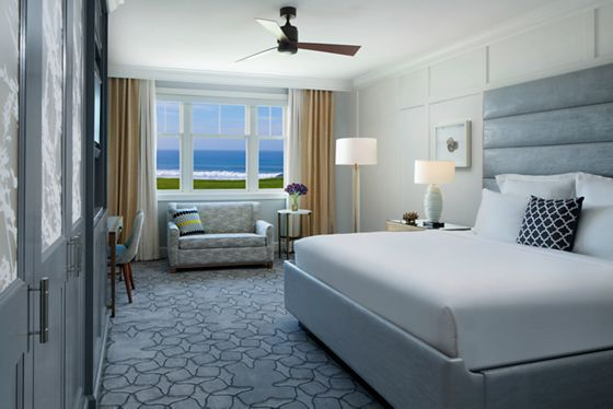 A room with a king bed, desk, loveseat and window overlooking the ocean