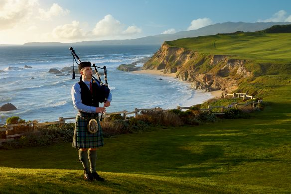 A man in traditional dress playing bagpipes with the ocean in the background
