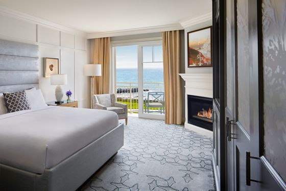 Room with a king bed, fireplace and an ocean-view terrace