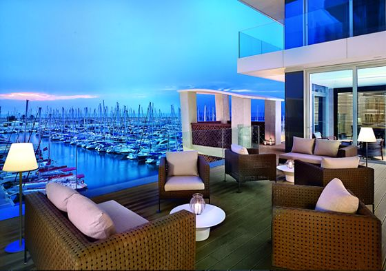 Spacious balcony with several seating areas overlooking the marina at dusk