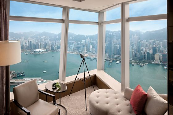 A corner room with large windows overlooks the water and city