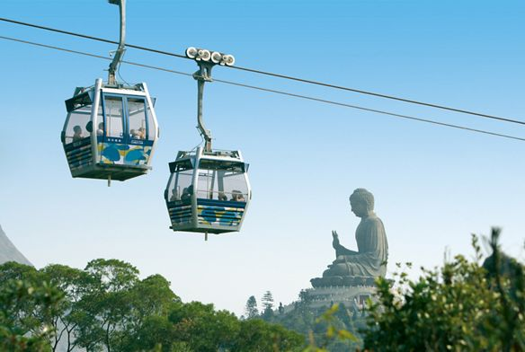 Two cable cars cross while a large Buddha statue sits in the background