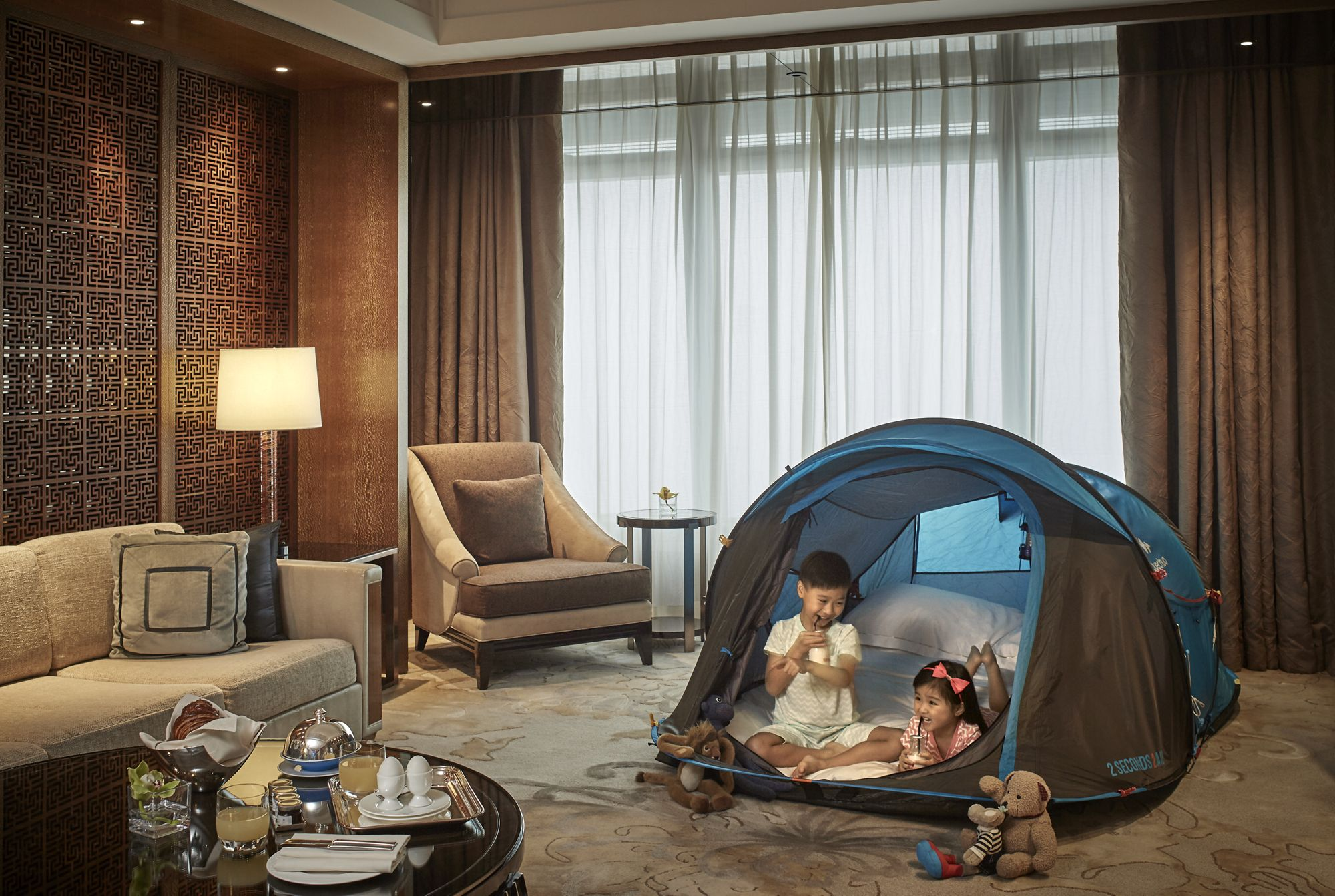 Two kids in a tent within a hotel guest room