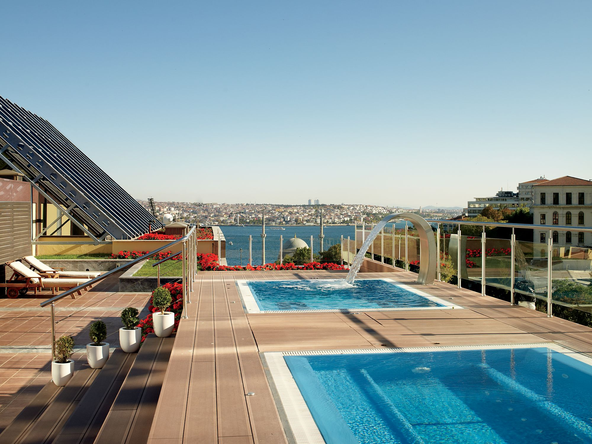 Outdoor space with steps leading up to two square whirlpools and a glass fence looking out over the water