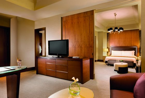 Two rooms divided by a wood sliding door that's open; one with a king bed and small table, the other a desk, sofa and TV