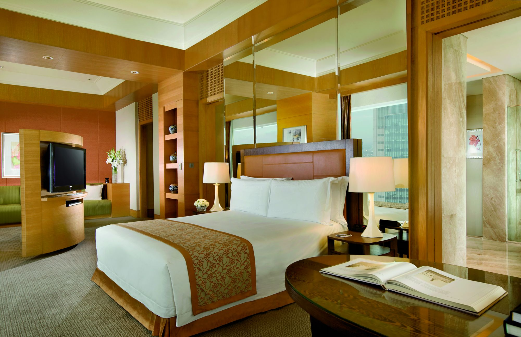Room with a king bed, an oval wood table with an open book on top, and a wood-paneled shelf with a flat-screen TV
