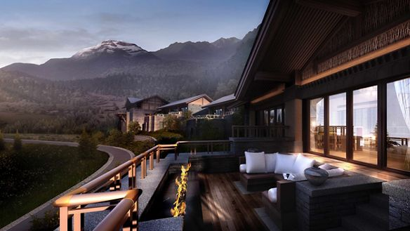 A mountain range overlooks a large terrace with a sofa and fireplace