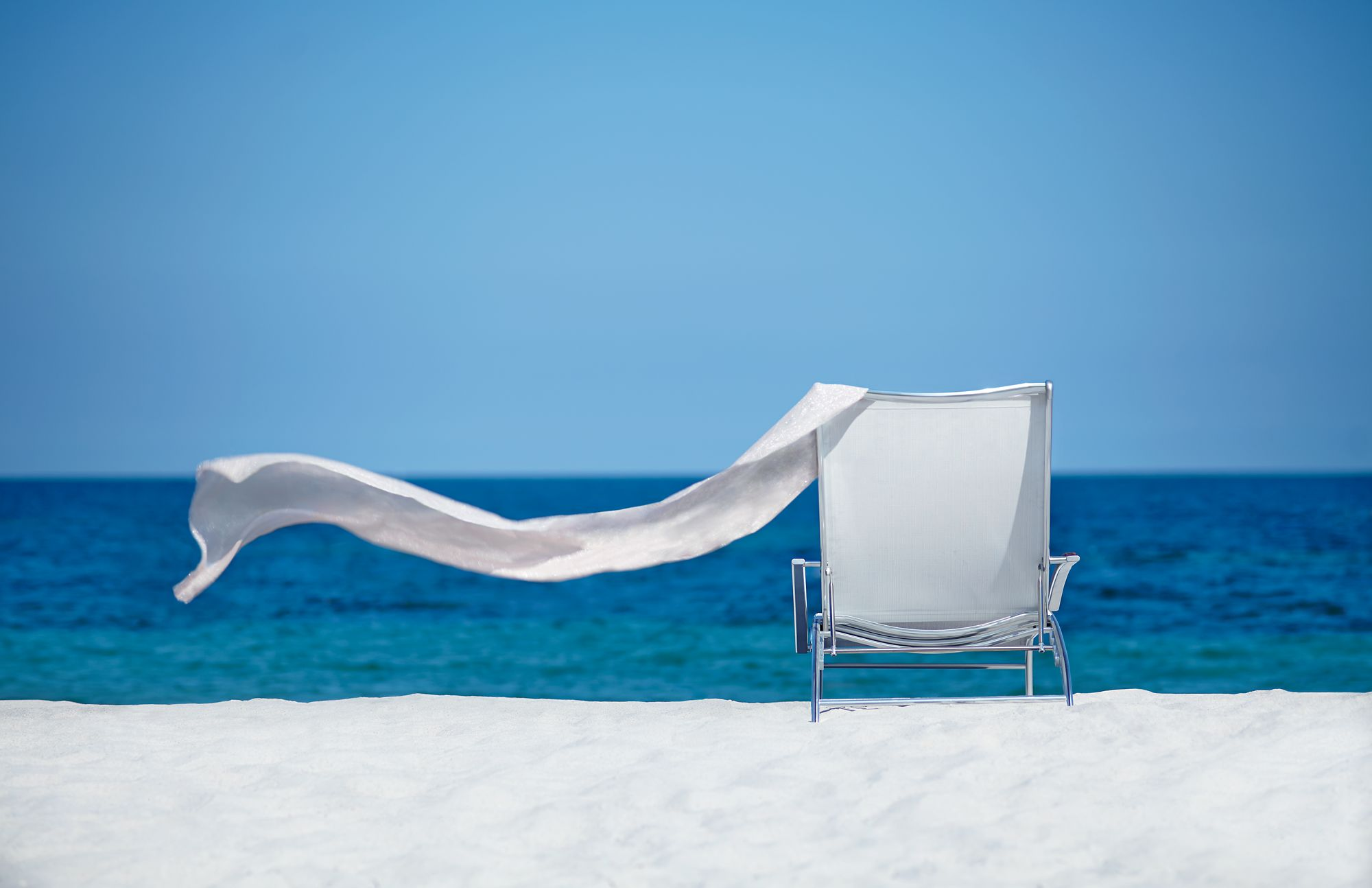 White lounge chair and towel blowing in the breeze by the ocean.