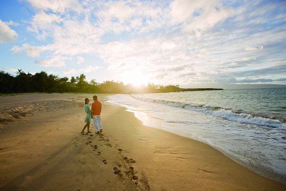A couple wanders along the pristine beach at sunset
